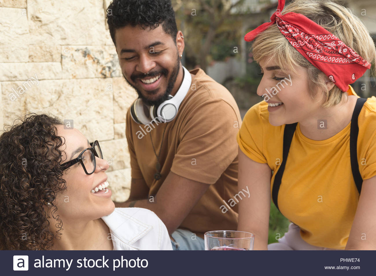 Cheerful young friends smiling and sitting  at restaurant outside. Group of people having fun together at cafe bar outdoor. Spring, warm, togetherness - Stock Image