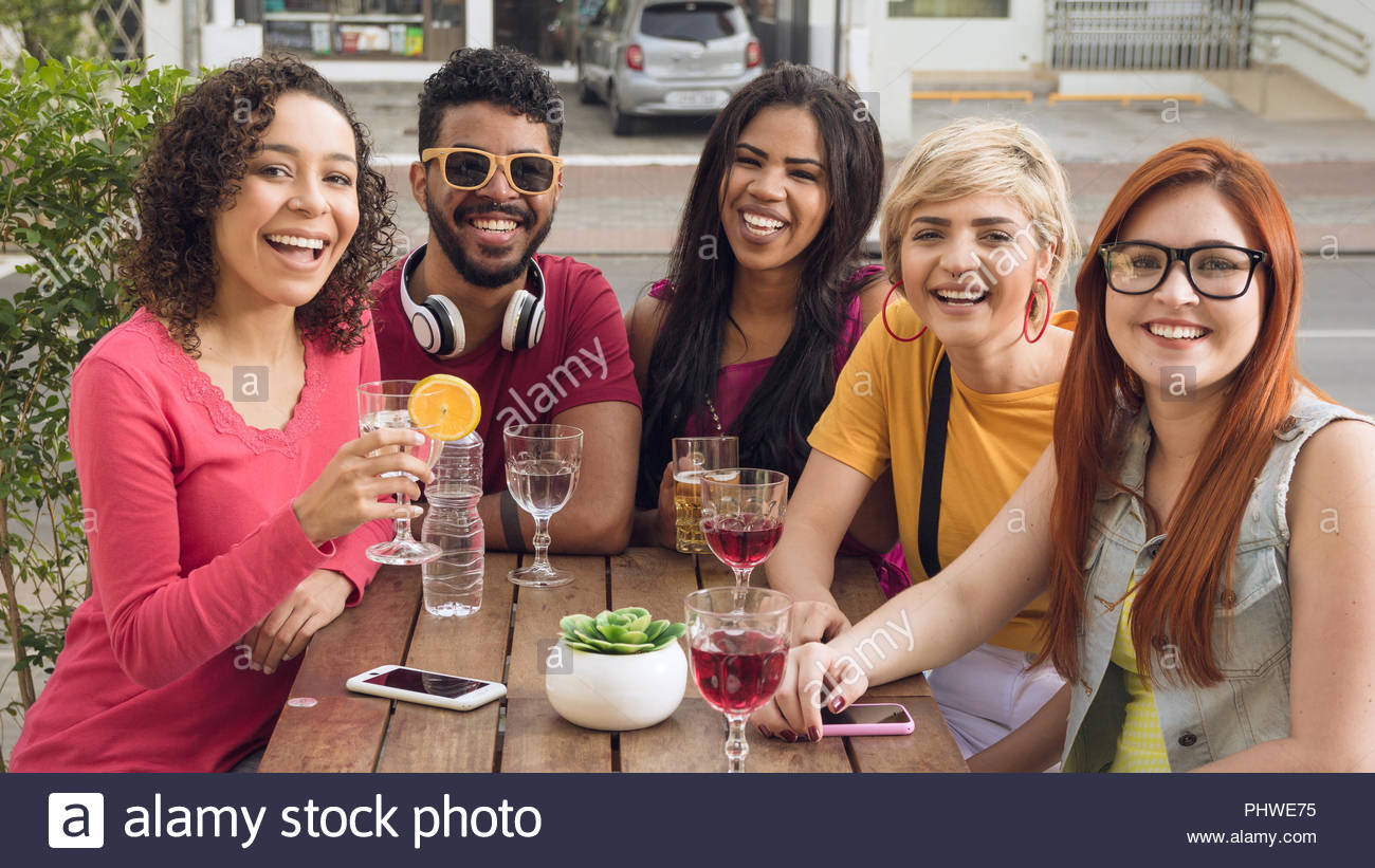 Cheerful young friends having a great time at cafe bar outdoor. Group of people socializing in a party at restaurant outside. Summer, warm, friendship - Stock Image