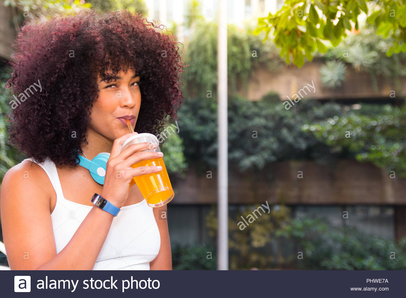 Portrait of gorgeous young woman drinking orange juice with headphones. She is black, on her early twenties, Afro style frizzy hair. building and tree - Stock Image