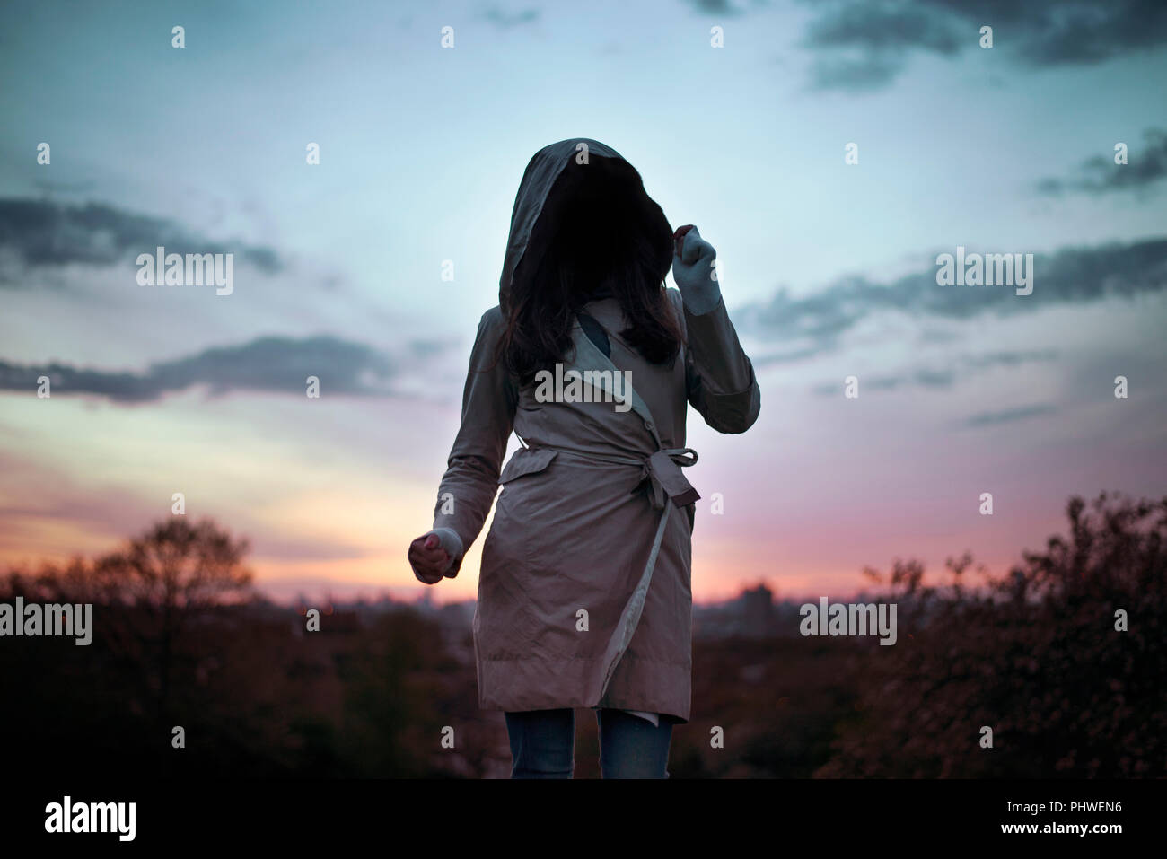 Unidentifiable woman wearing hooded trench coat dancing in the sunset. Mysterious, creative - travel / lifestyle concept. London, UK - Stock Image