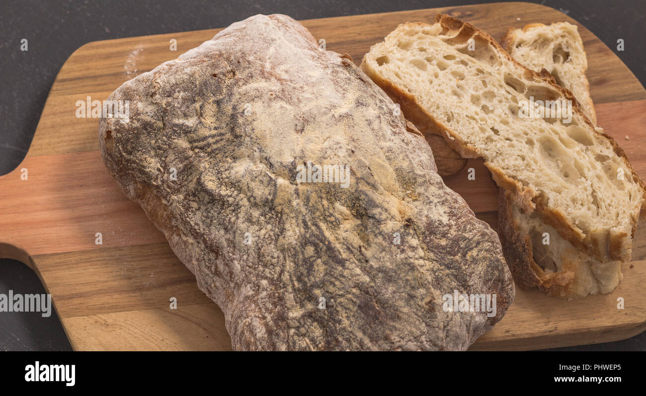 Bread and slices on wooden bread board - Selective focus on rustic bread close up Stock Photo