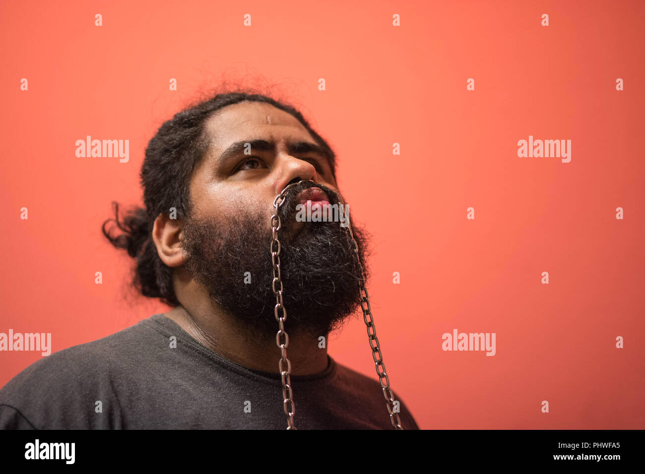 Bearded man holding up a chain in his face - Stock Image