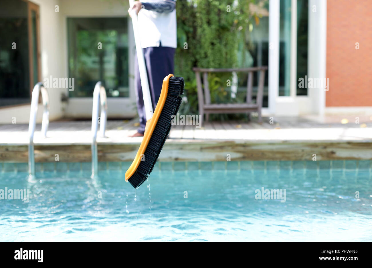 Mna is cleaning a swimming pool with a brush - Stock Image