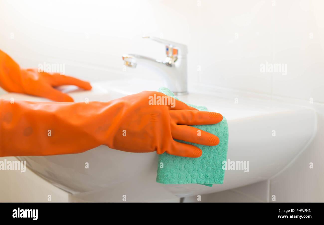 Woman cleaning water tap witn orange glove Stock Photo