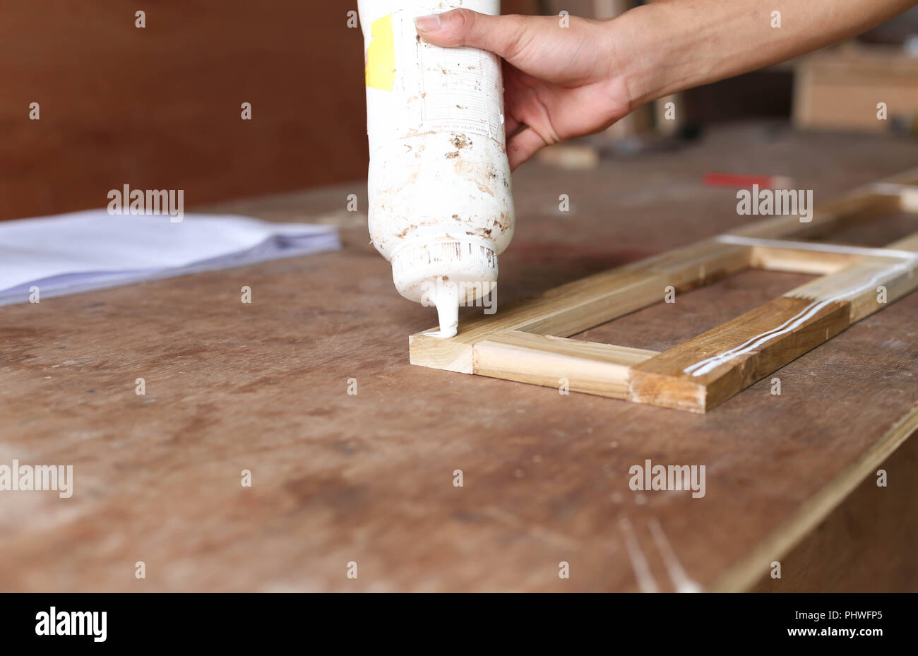 Carpenter putting glue on a piece of wood - Stock Image