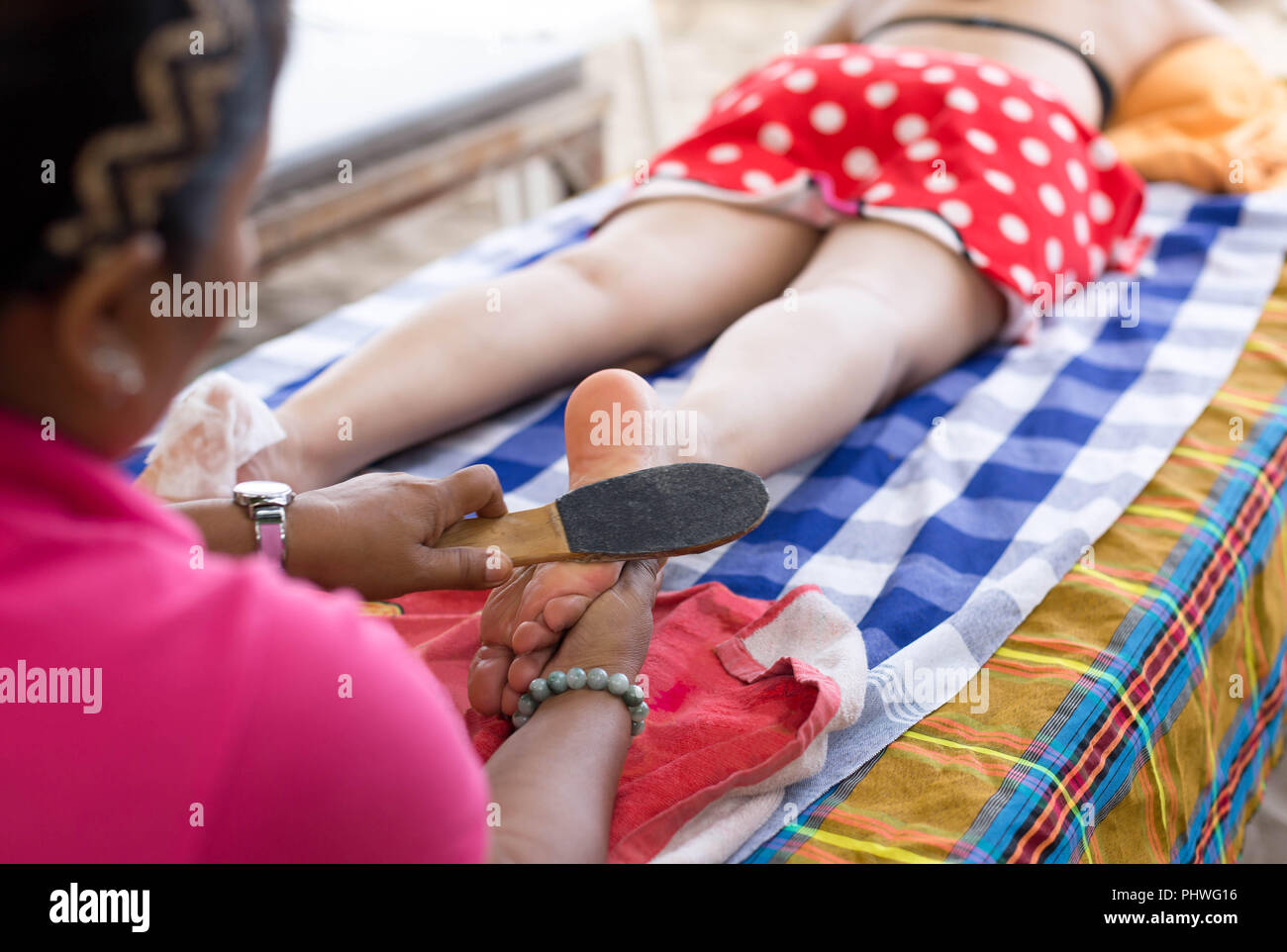 Woman having foot scrub on the beach - Stock Image