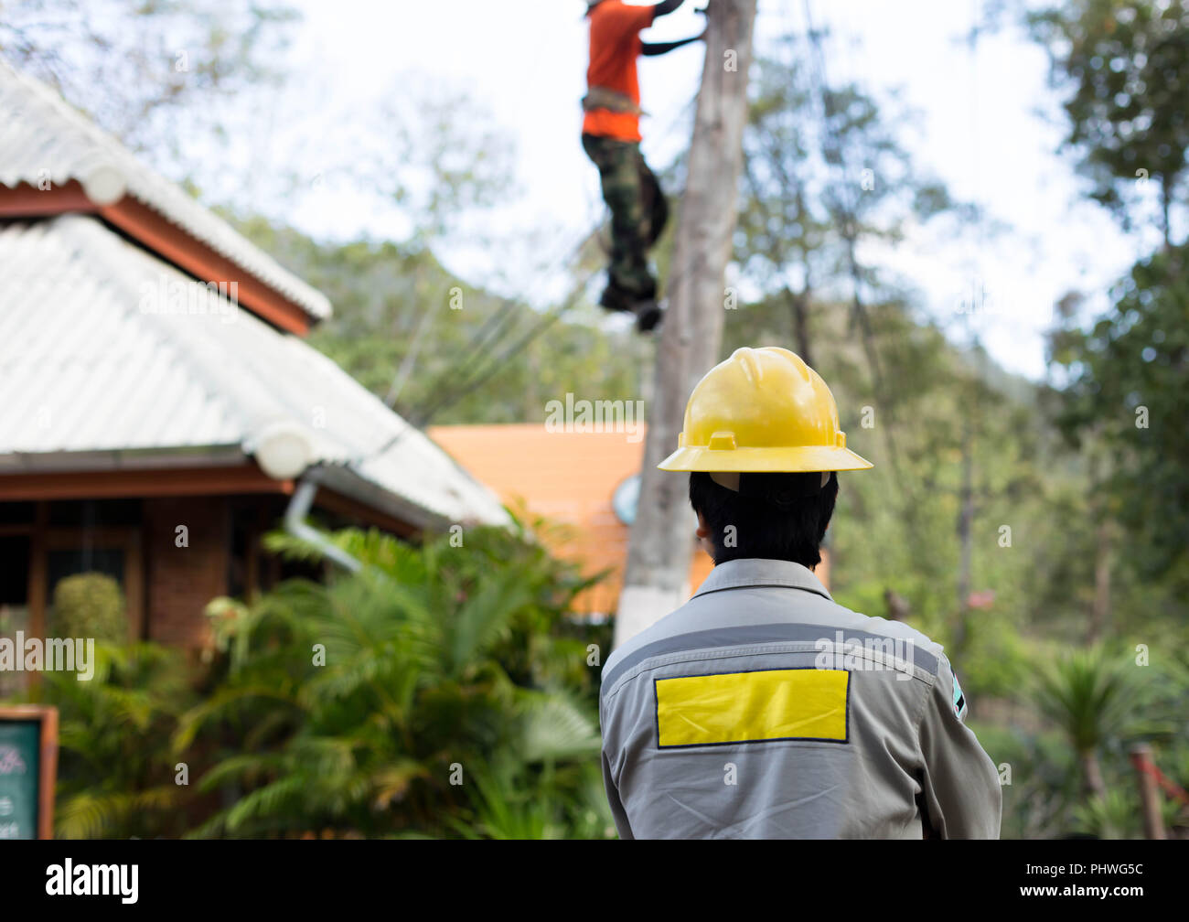 Electrician lineman repairman worker on electric post power pole - Stock Image