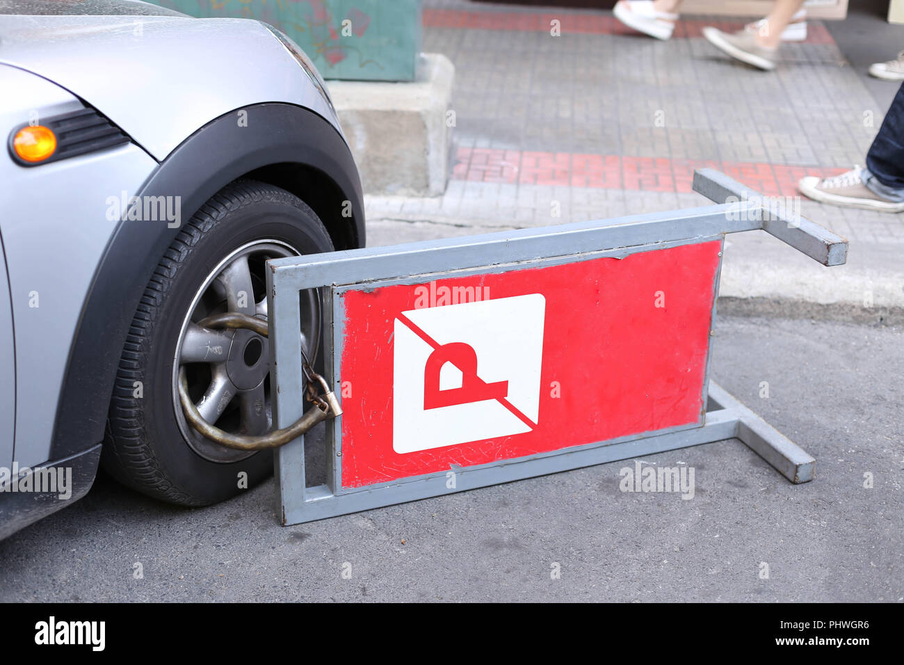 clamped front wheel of illegally parked car  - Stock Image