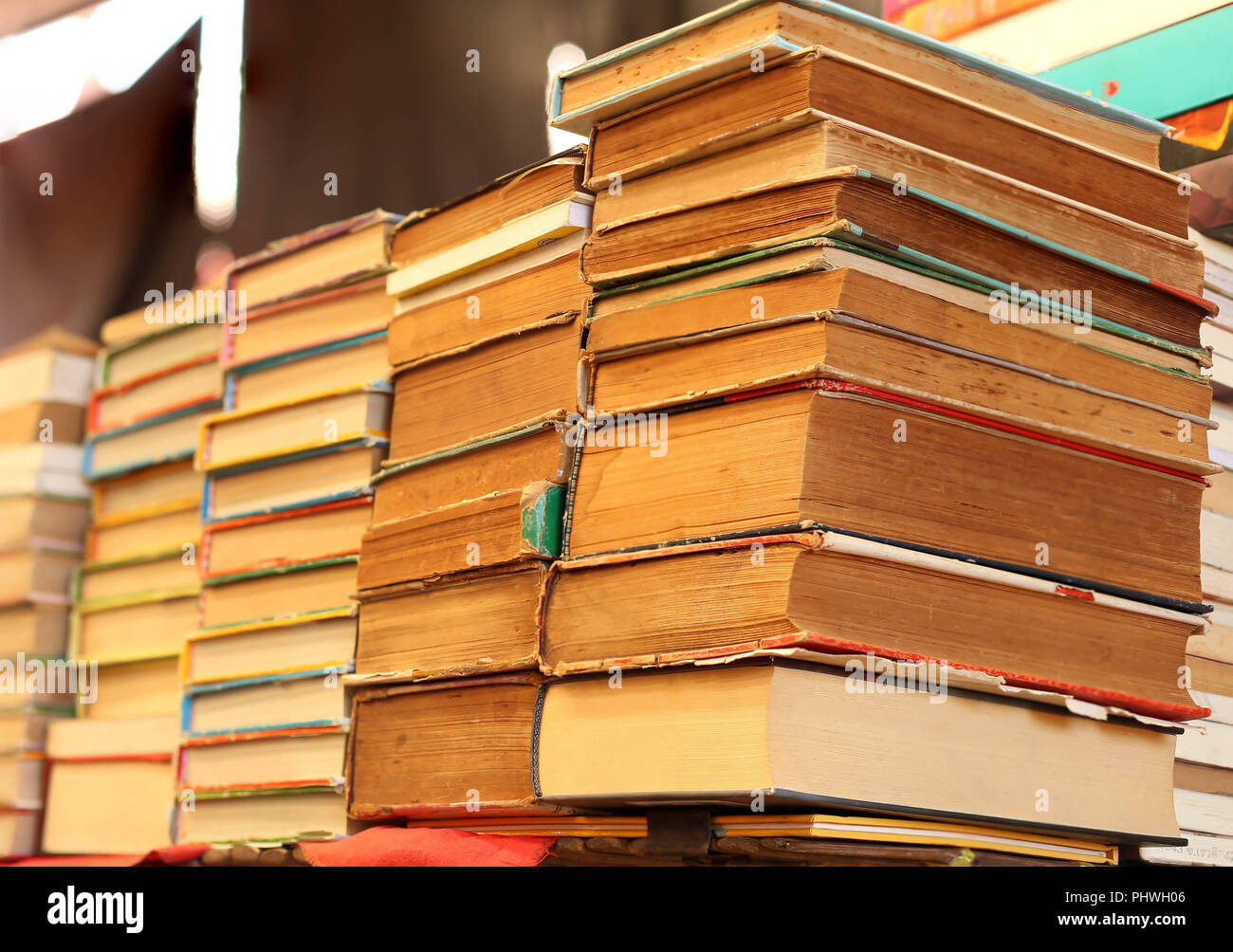 Piles of old books on a table in blur background. - Stock Image