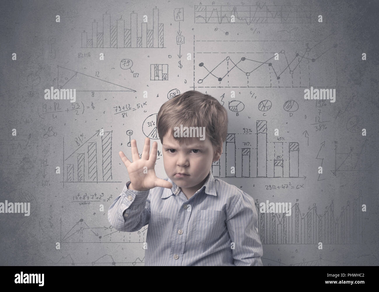 Little boy in front of a grey wall with graphs and statistics around - Stock Image