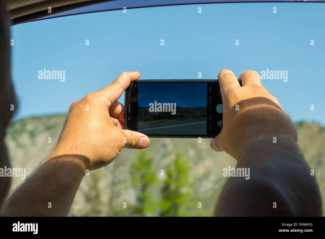 A young man pulling two hairy hands into the open window of a moving car holds a smartphone taking a photo of the mountains in the Altai with blue cle - Stock Image