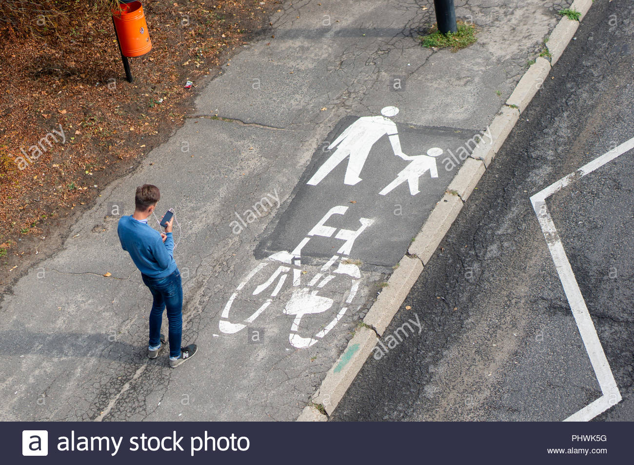 Young man looking at his phone while standing on a sidewalk for bicycles and pedestrians in the city from aerial perspective - Stock Image