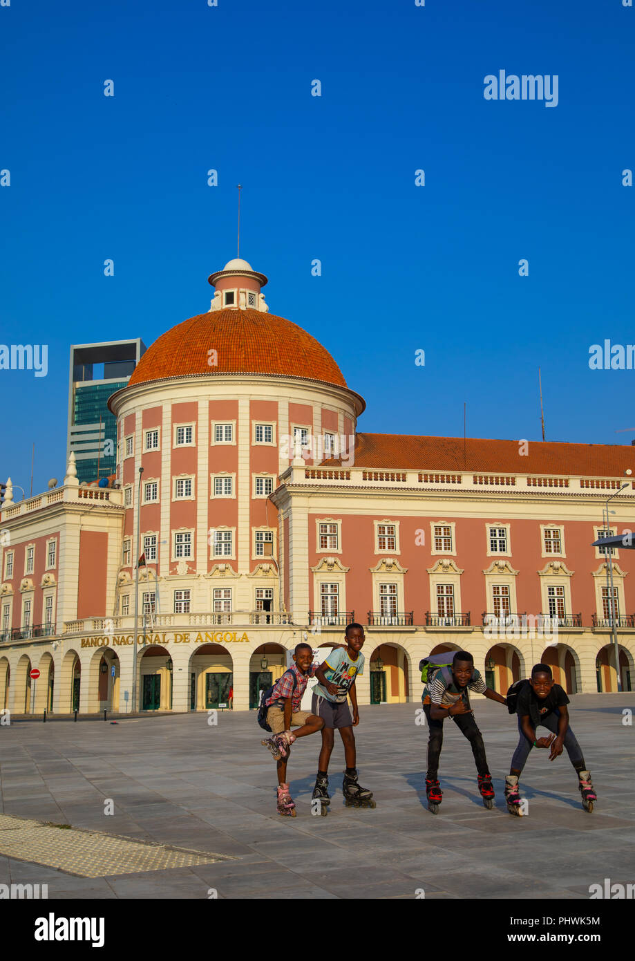 Angola teenage boys wirth roller skating in front of banco nacional de angola, Luanda Province, Luanda, Angola - Stock Image