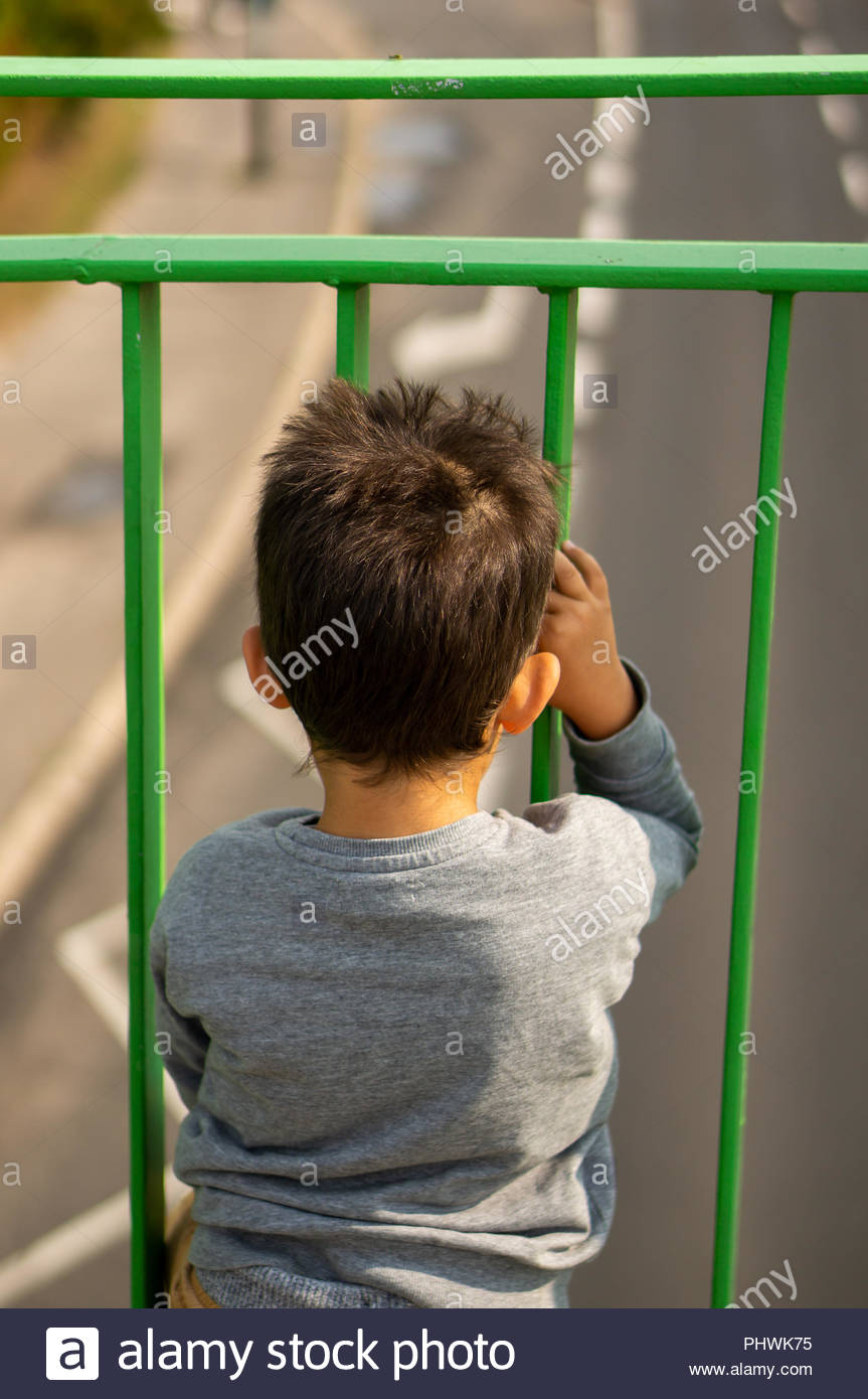 Young boy looking through a  metal barrier from a bridge at a asphalt road in soft focus - Stock Image