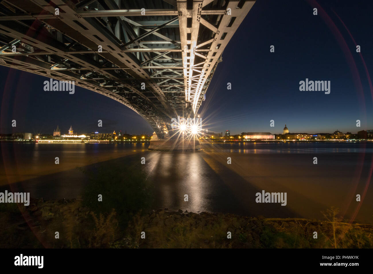 Picture with red lense flare of the German city of Mainz with Theodor Heuss Bridge seen from Wiesbaden - Stock Image