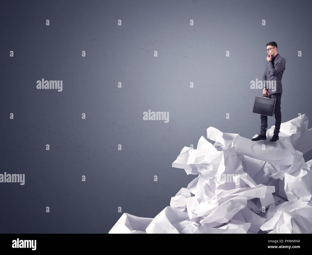 Thoughtful young businessman standing on a pile of crumpled paper with a dark grey background - Stock Image