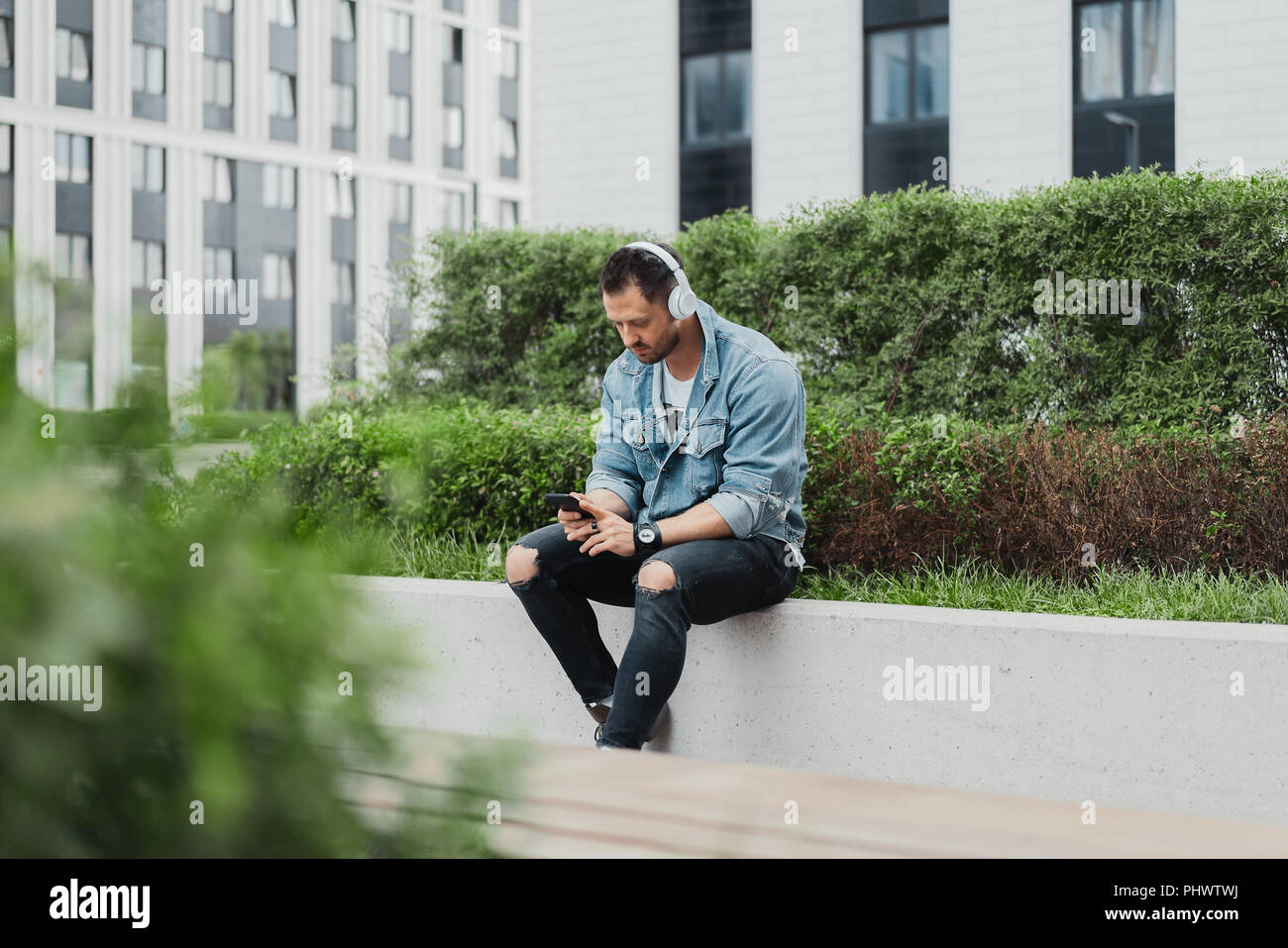 Young attractive man listening to music in earphones in cityscape. - Stock Image
