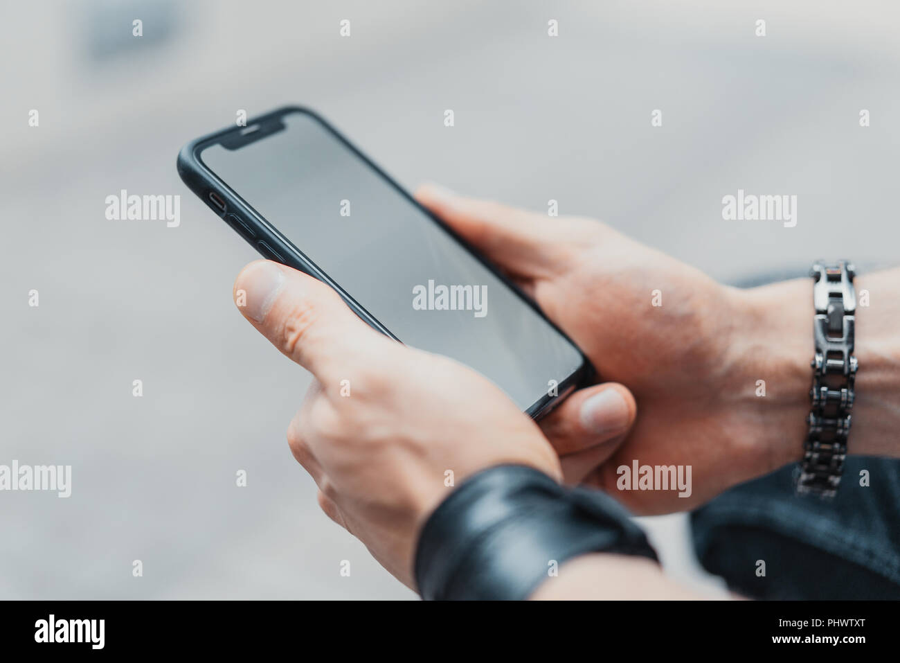 Young man holding black mobile phone . - Stock Image