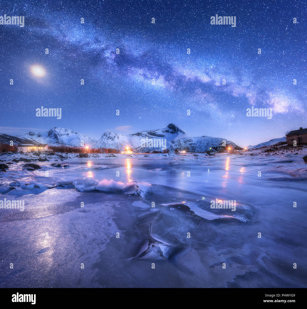 Milky Way above frozen sea coast, snow covered mountains and starry sky with moon in winter at night in Norway. Landscape with galaxy, ice, snowy rock - Stock Image