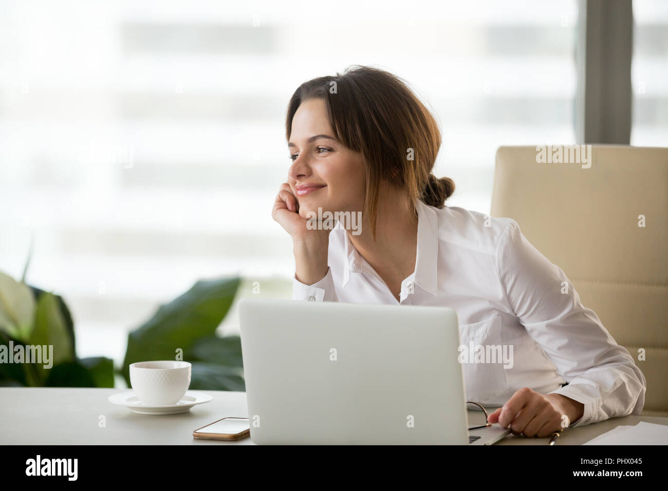 Smiling happy businesswoman feeling motivated dreaming about fut - Stock Image