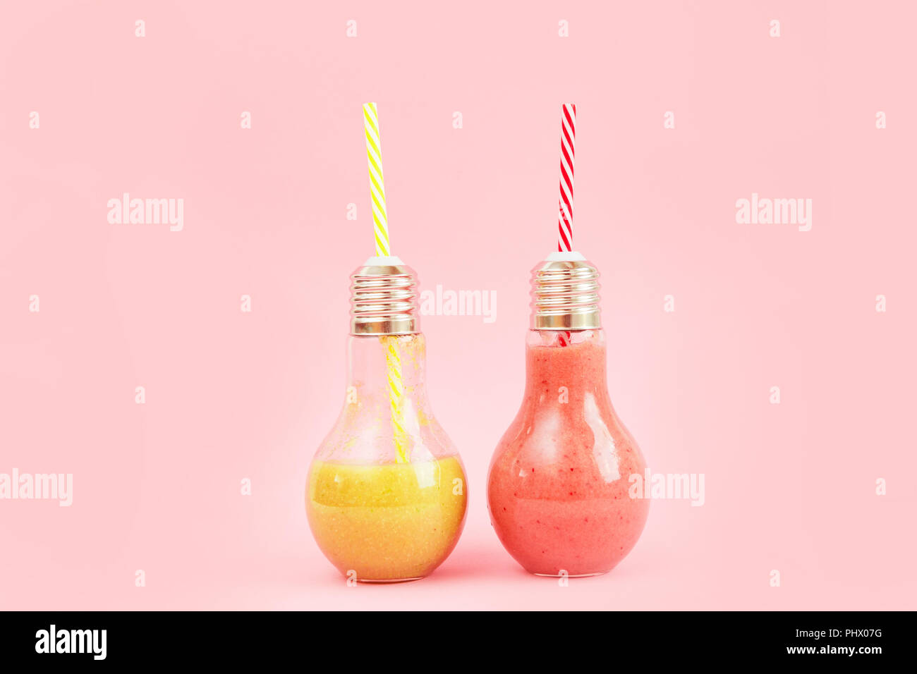 Two lamp- shaped jars with fruit smoothies isolated on pink background. Stock Photo