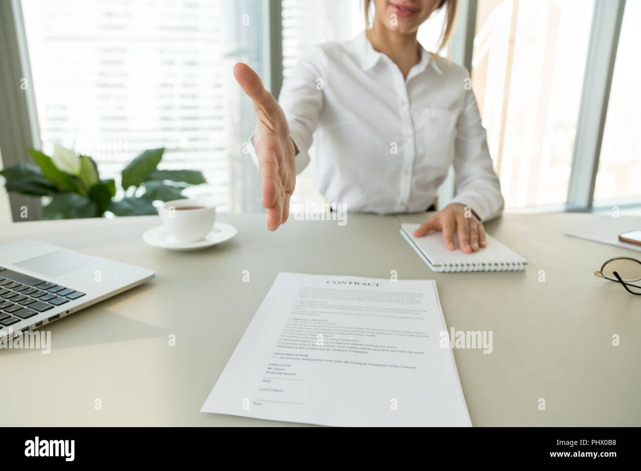 Businesswoman employer extending hand for handshake offering sig - Stock Image