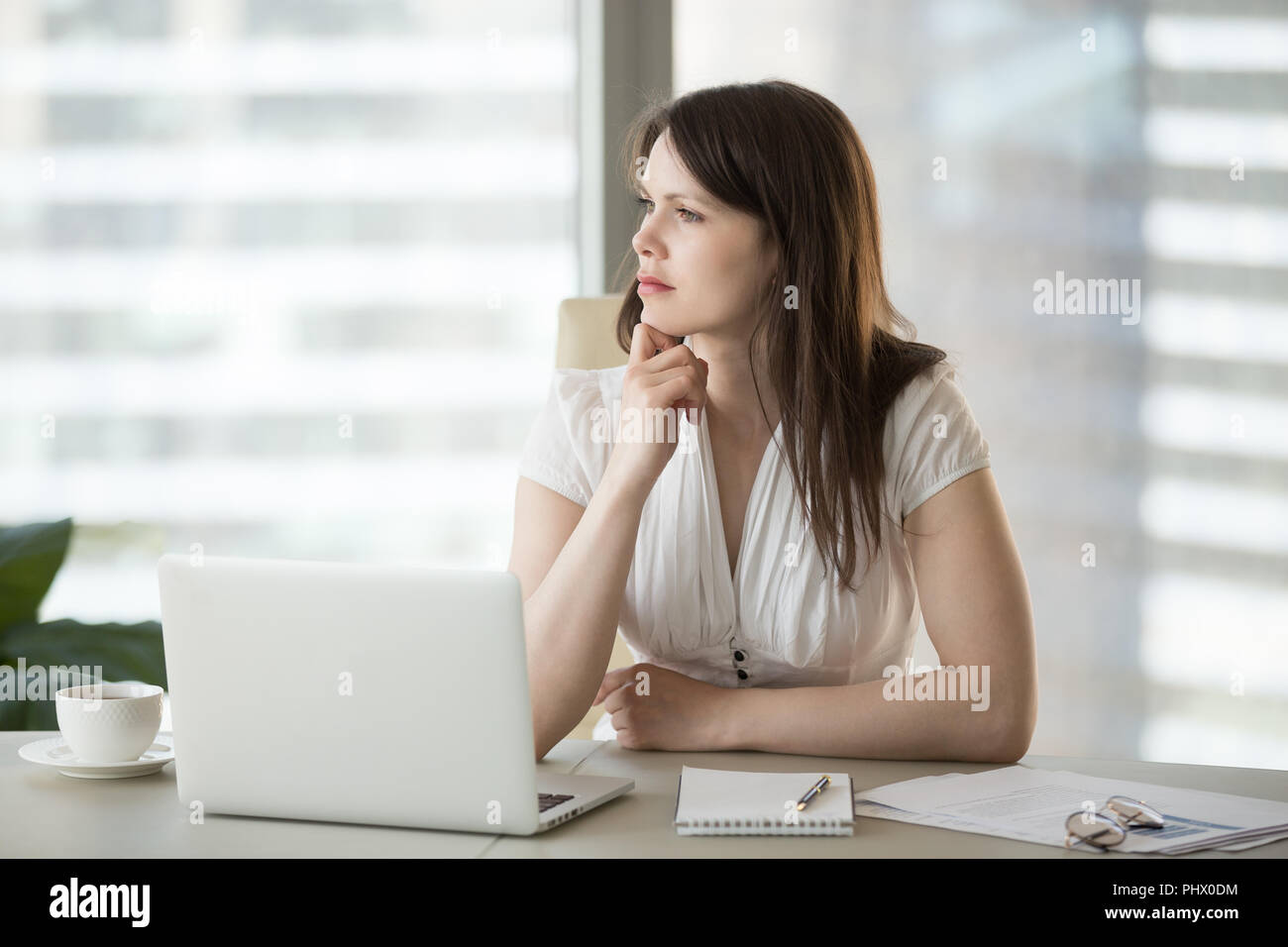 Thoughtful doubtful businesswoman looking away thinking of probl - Stock Image