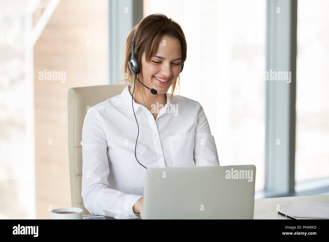 Smiling telemarketer wearing headset consulting customer making  - Stock Image