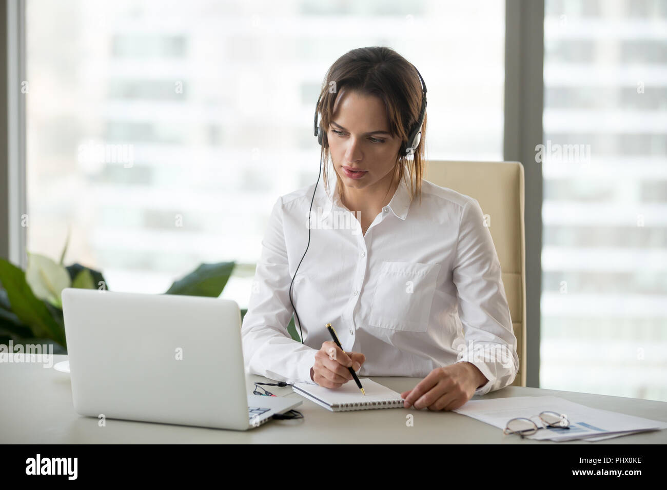 Serious businesswoman in headphones watching webinar on laptop m - Stock Image