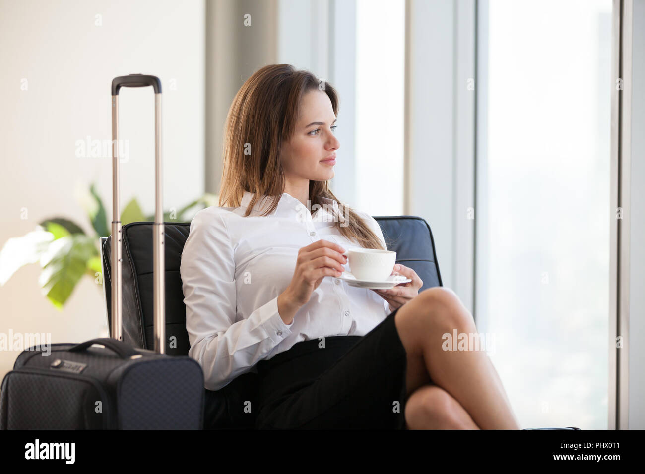 Thoughtful businesswoman drinking coffee with baggage in airport - Stock Image