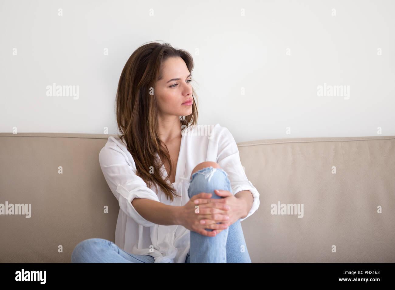 Thoughtful pensive millennial woman sitting on sofa feeling lone - Stock Image