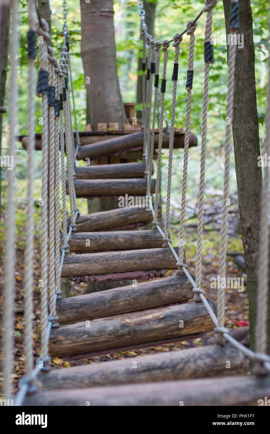 Rope bridge at adventure climbing park with focus on foreground - Stock Image