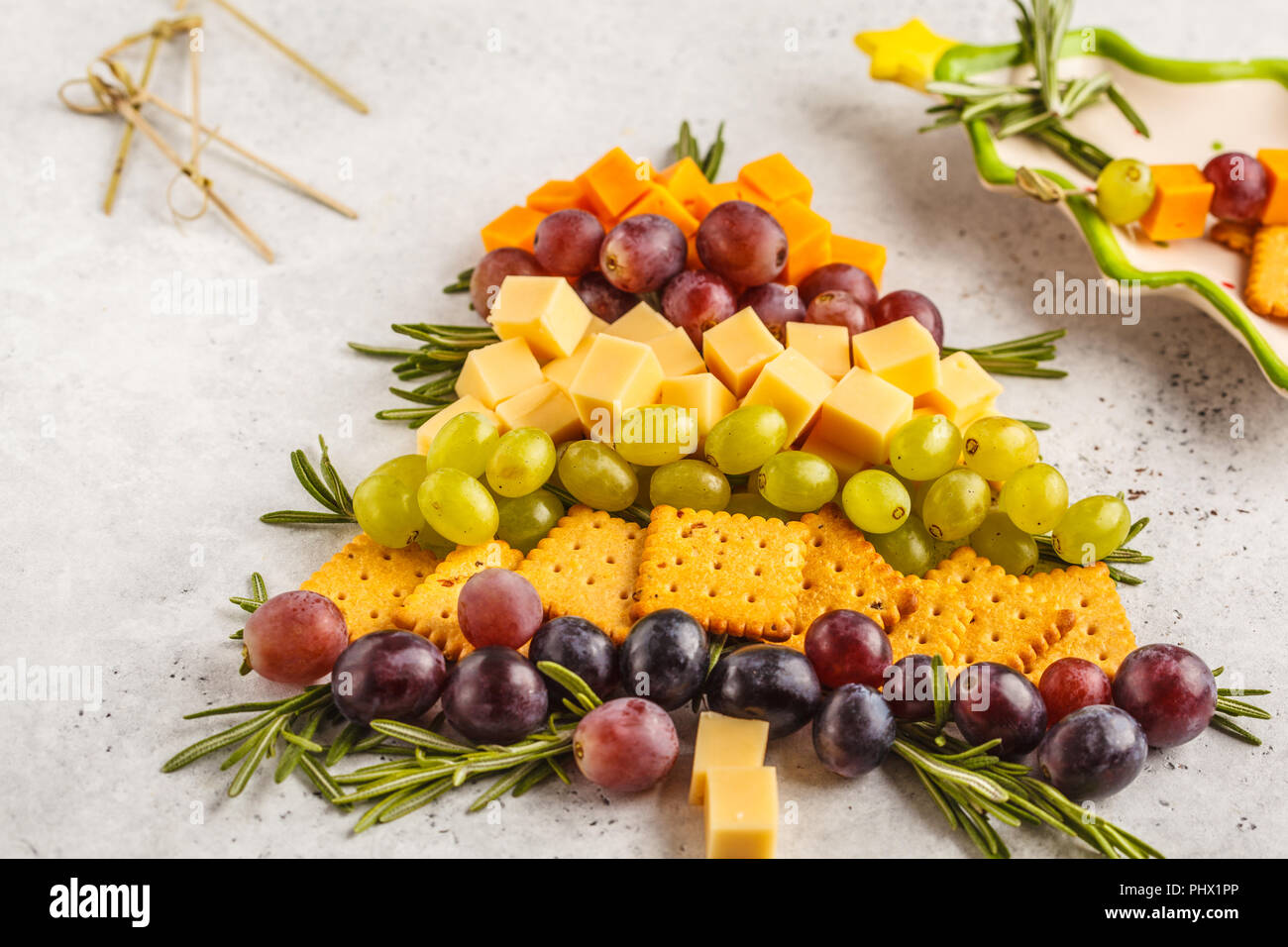 Christmas tree from appetizers: cheese, grapes, crackers. Christmas food concept, white background. - Stock Image
