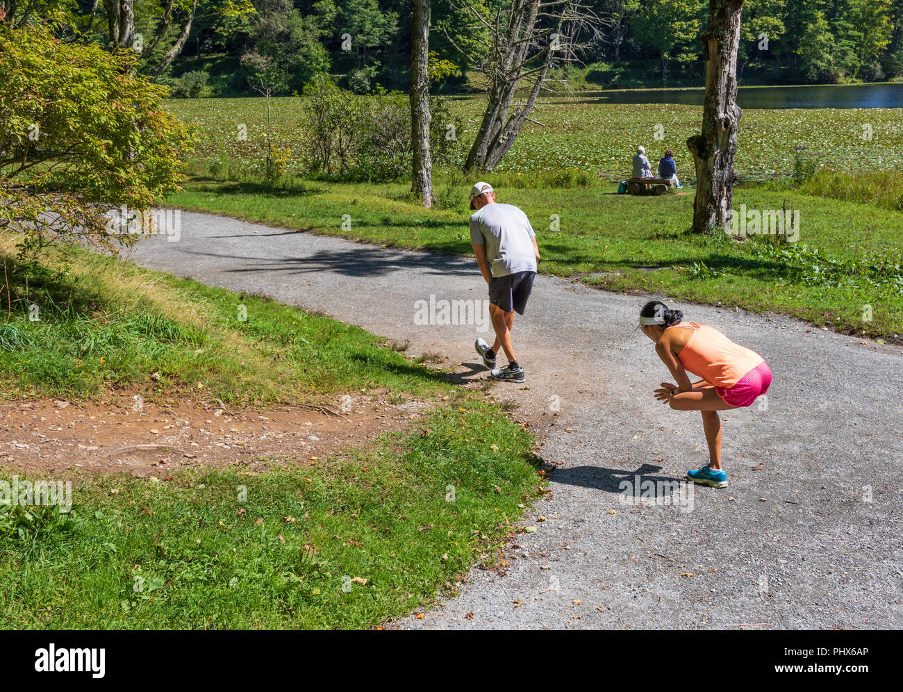 BLOWING ROCK, NC, USA-8/23/18: Two runners, male and female, stretching prior to running around Bass Lake and two women sit on a bench near the lake. Stock Photo