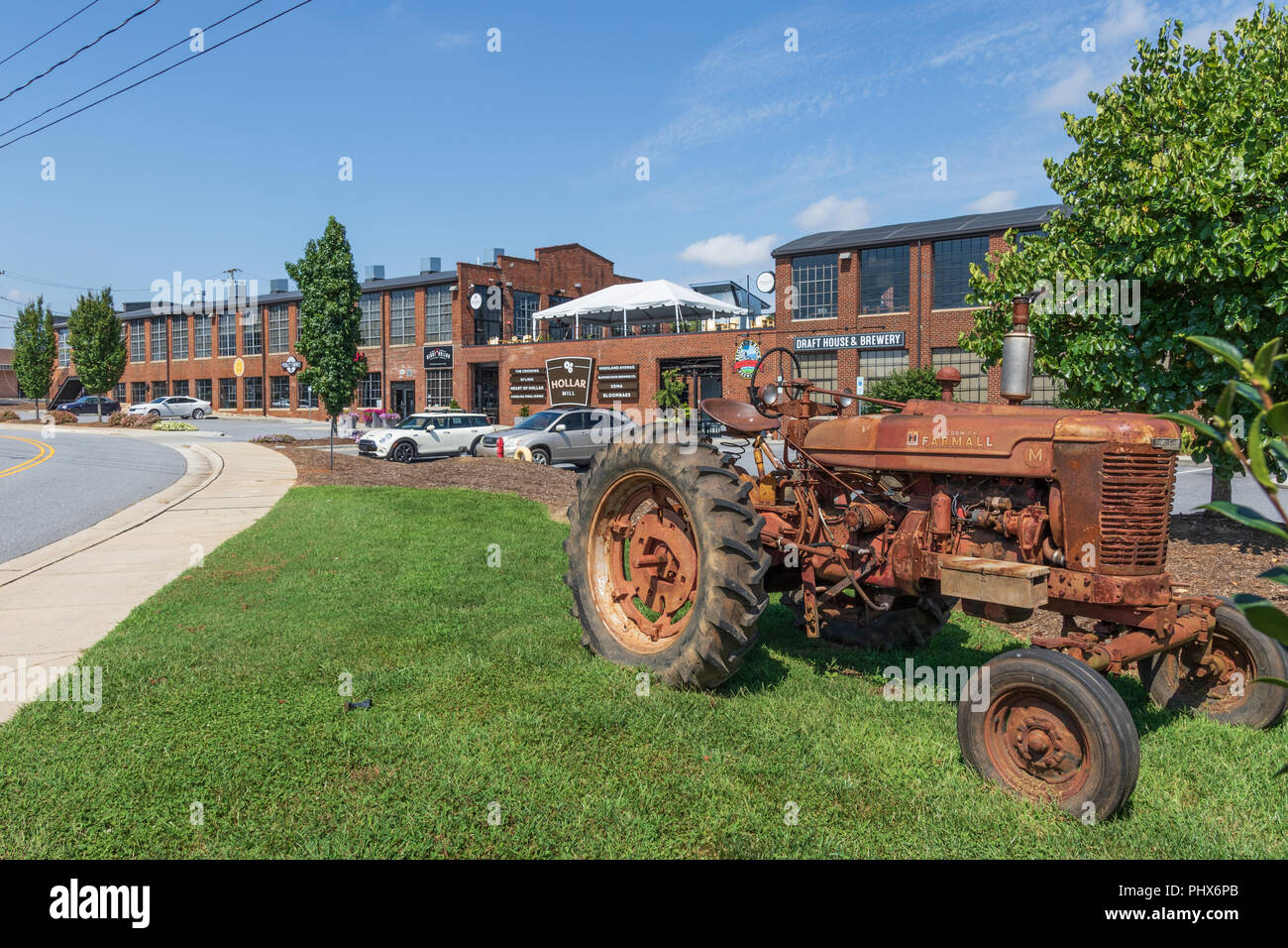 HICKORY, NORTH CAROLINA,  USA-9/1/18:  Hollar Mill, a renovated mill building, containing specialty stores and shops, with antique Farmall tractor. Stock Photo