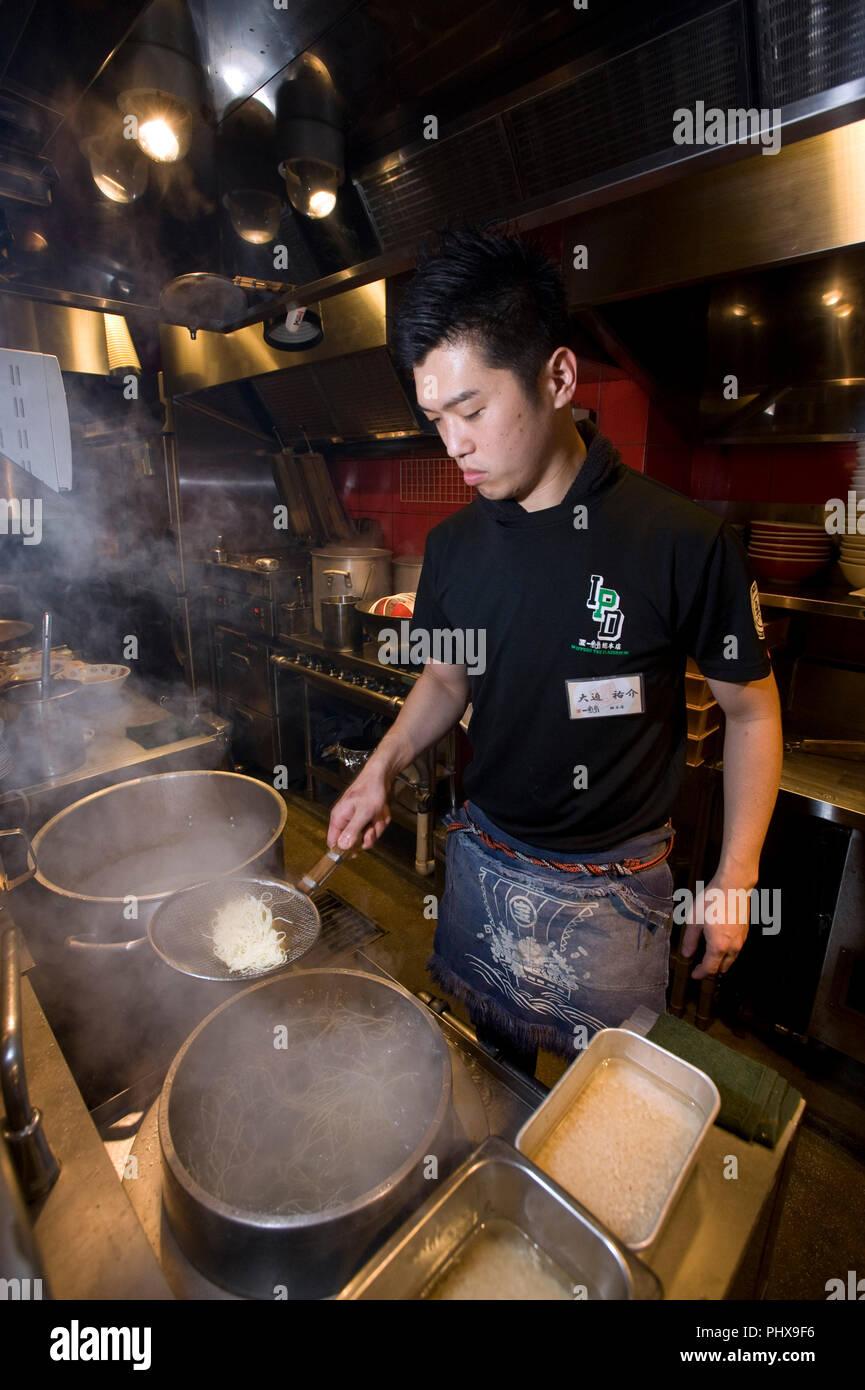 Store manager Yusuke Osako prepares noodles in the kitchen at Hakata Ippudo Ramen's main store in the Daimyo district of Fukuoka City, Fukuoka Prefect - Stock Image