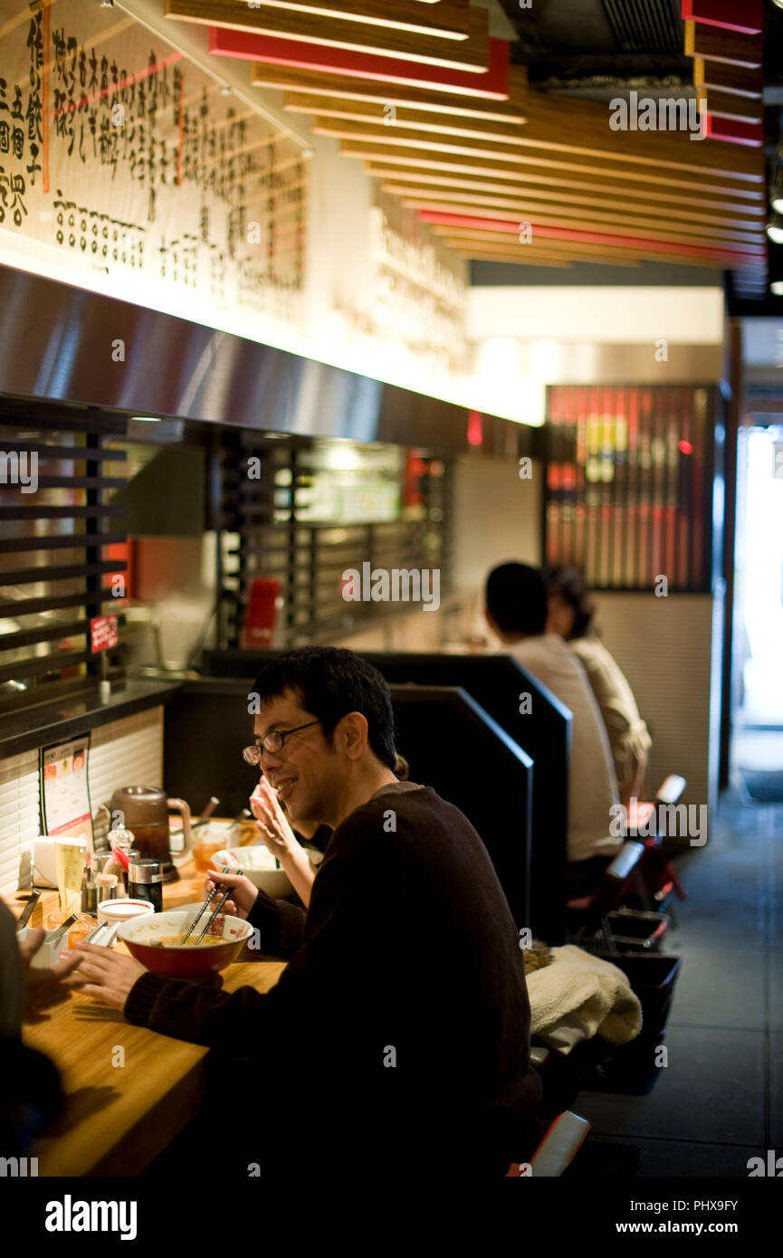 Customers enjoy soup noodles prepared at Hakata Ippudo Ramen's main store in the Daimyo district of Fukuoka City, Fukuoka Prefecture Japan on 08 March Stock Photo