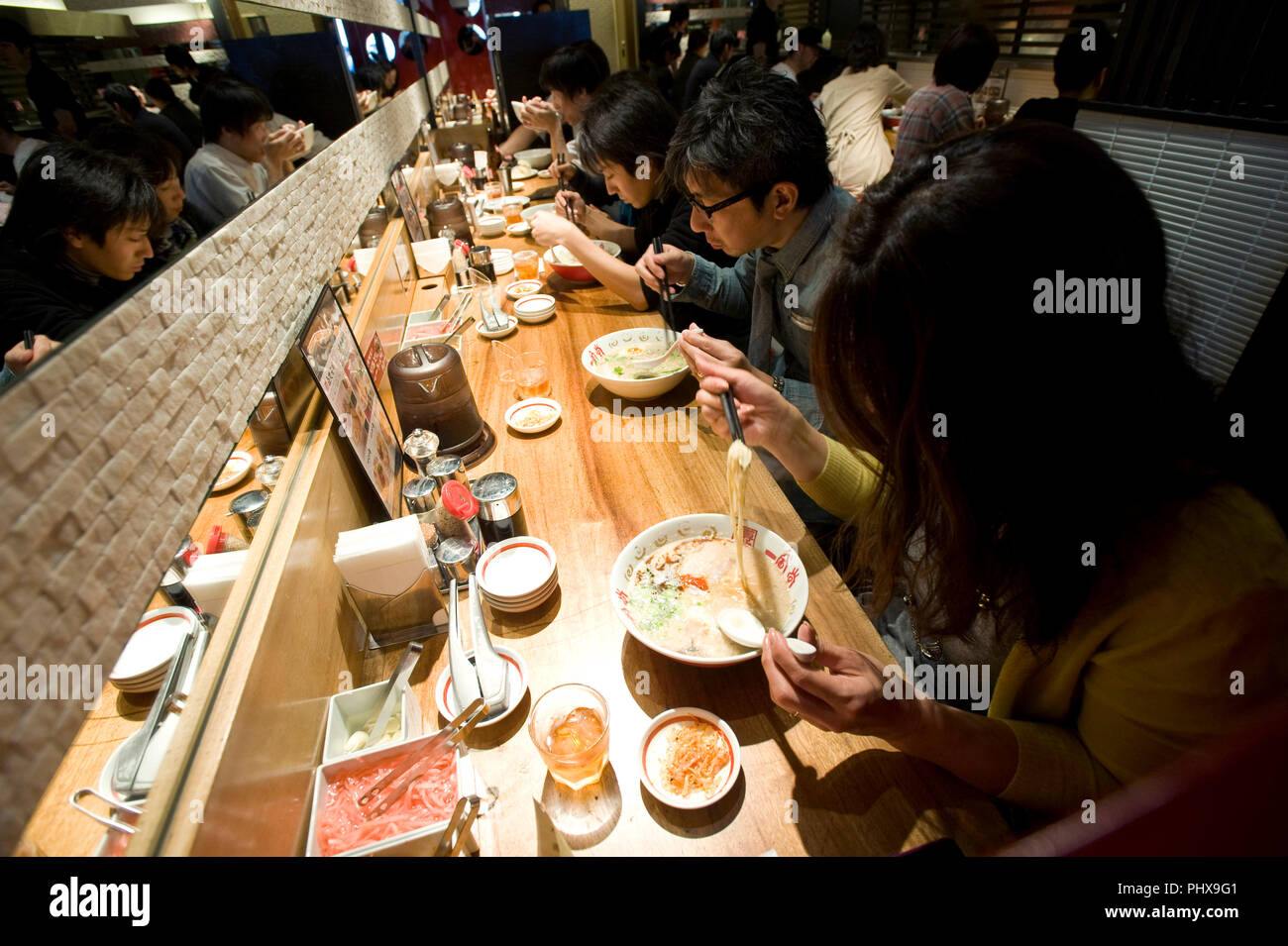 Customers enjoy soup noodles prepared at Hakata Ippudo Ramen's main store in the Daimyo district of Fukuoka City, Fukuoka Prefecture Japan on 08 March - Stock Image