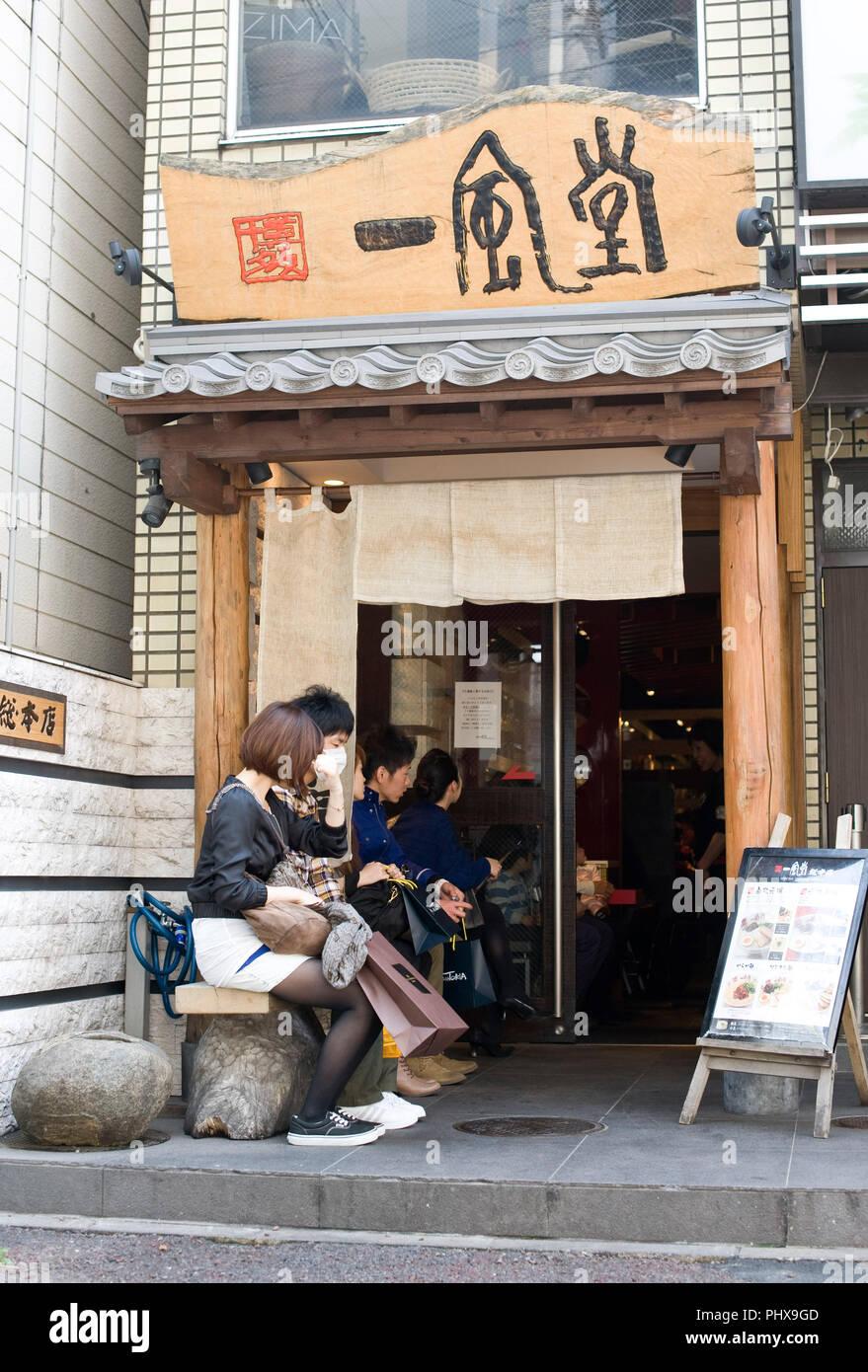 Customers line up to enjoy soup noodles prepared at Hakata Ippudo Ramen's main store in the Daimyo district of Fukuoka City, Fukuoka Prefecture Japan  - Stock Image