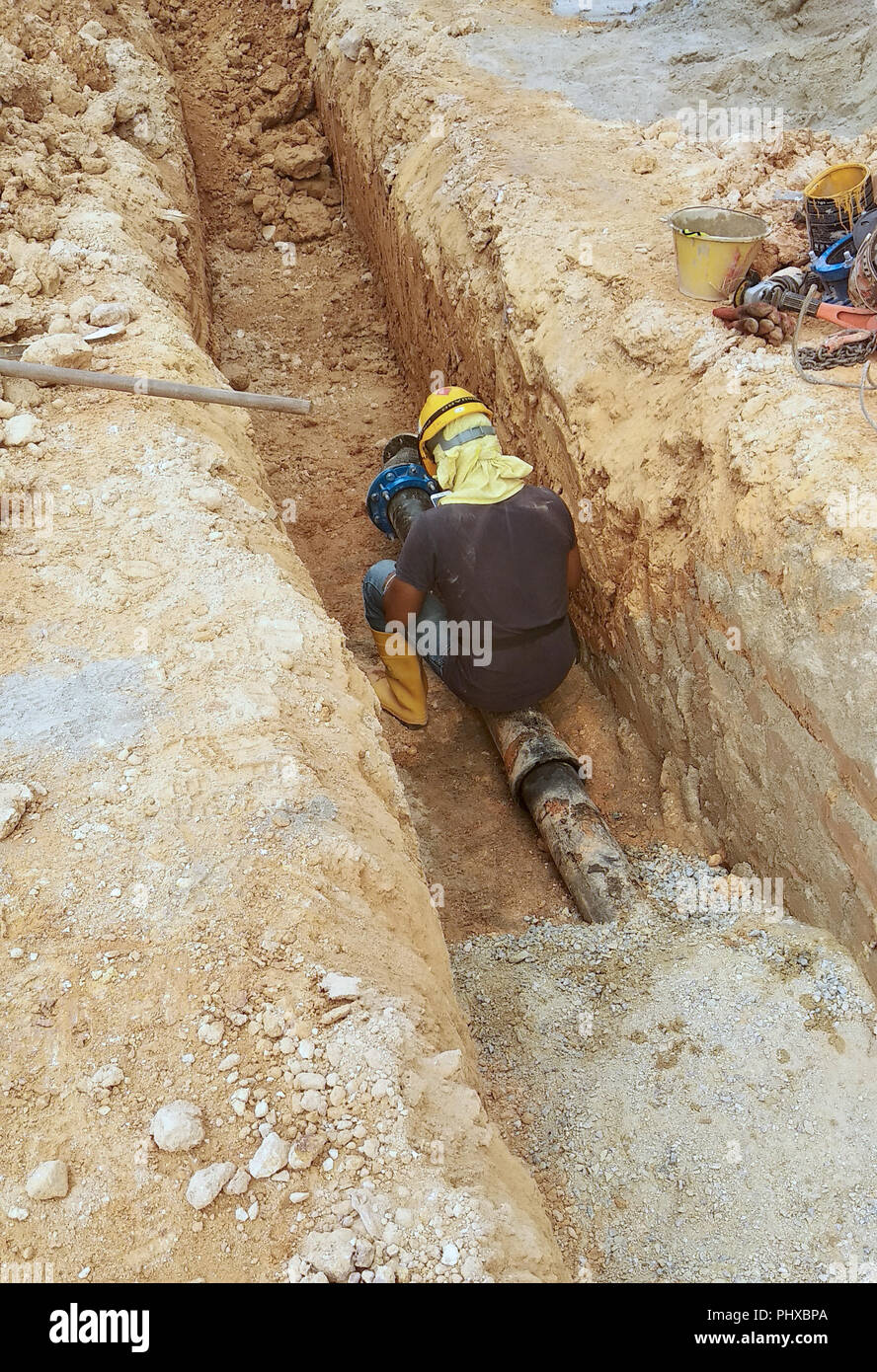 Underground utility and services pipe laid by workers in the trenches at the construction site. Installation of pipe joint and elbow in progress. - Stock Image