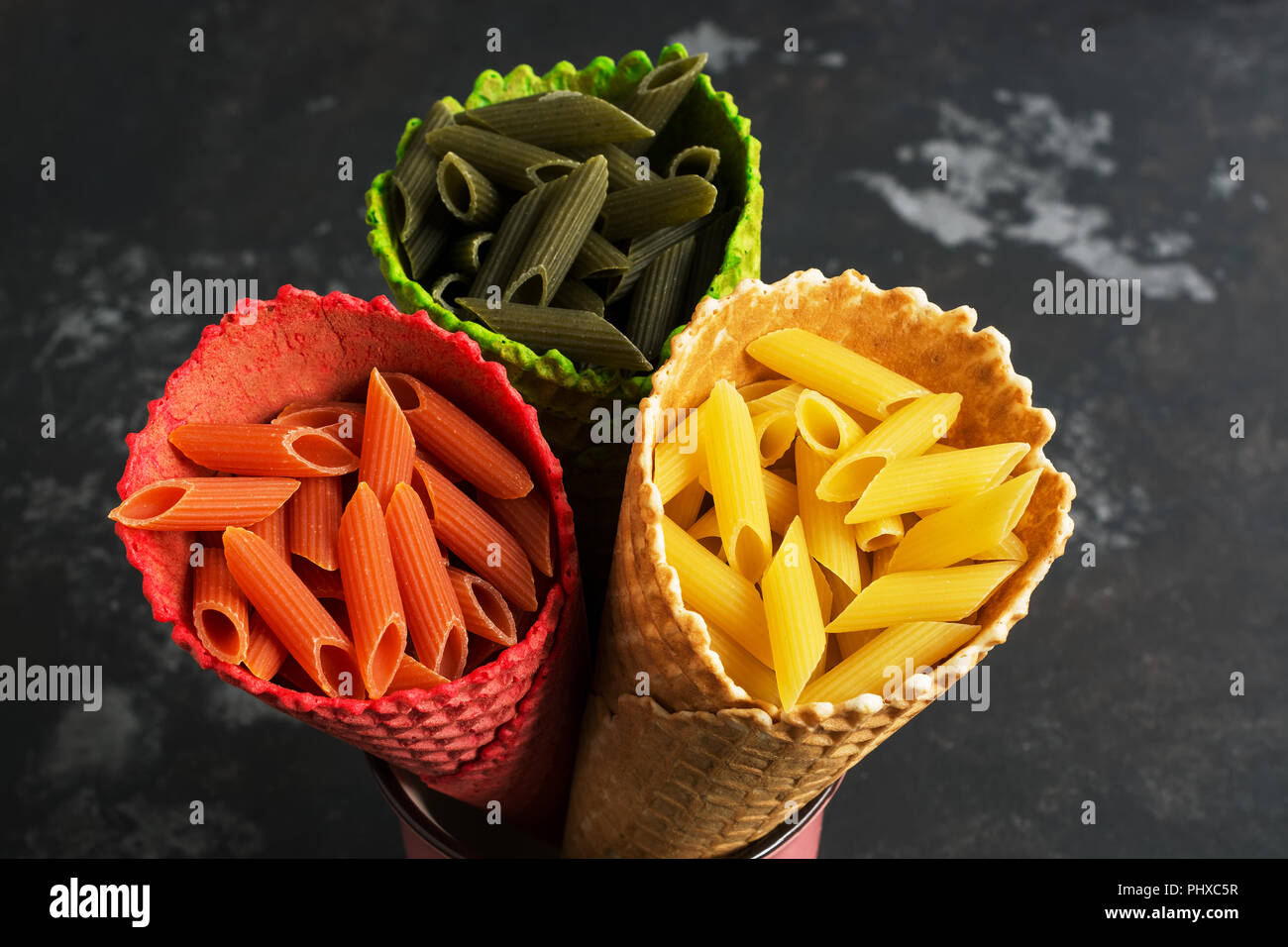 Colored macaroni close-up in waffle colored horns. The concept of color and food. View from above, flat lay Stock Photo