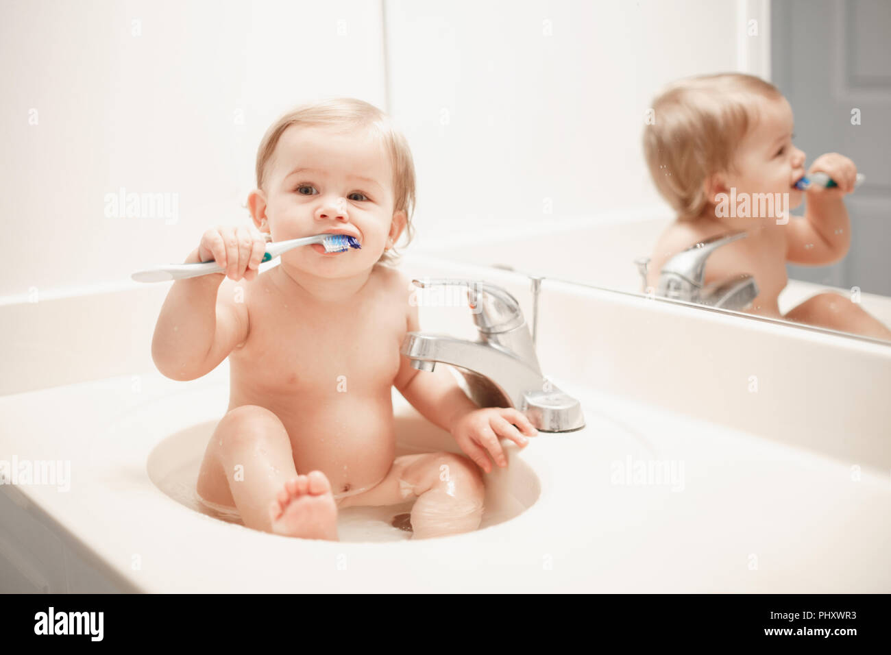 Portrait of cute Caucasian blonde funny baby girl boy sitting in washroom sink with water. Child brushing teeth. Happy healthy childhood concept. Ever Stock Photo