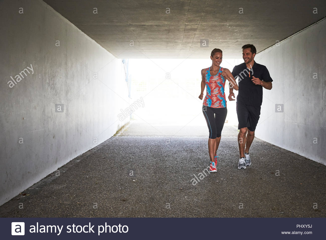 Young couple jogging in tunnel - Stock Image