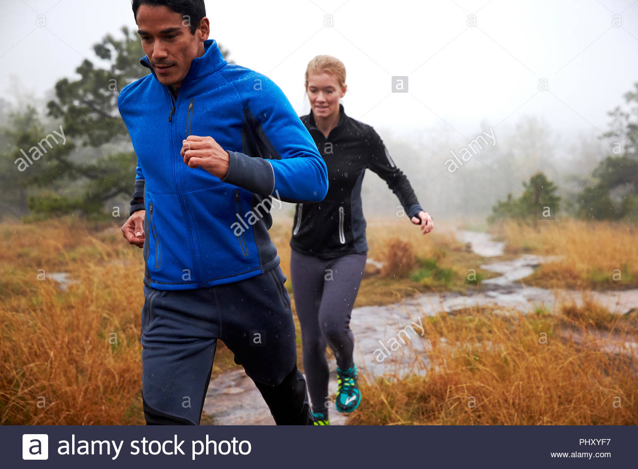 Young couple running in a river - Stock Image