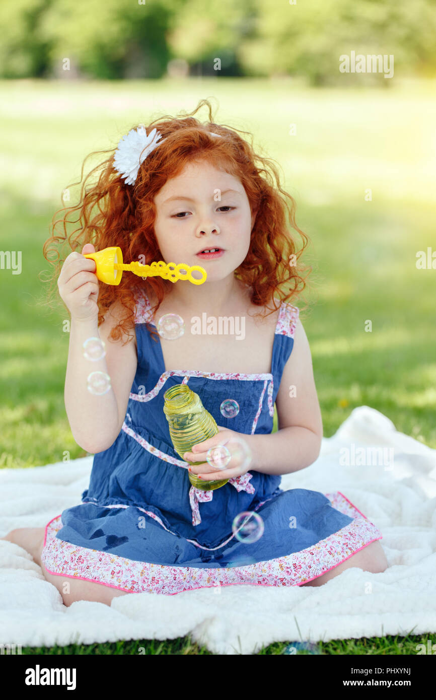 Portrait of cute funny little red-haired Caucasian girl toddler in blue dress in park outside, child blowing soap bubbles, bright summer day, lifestyl - Stock Image