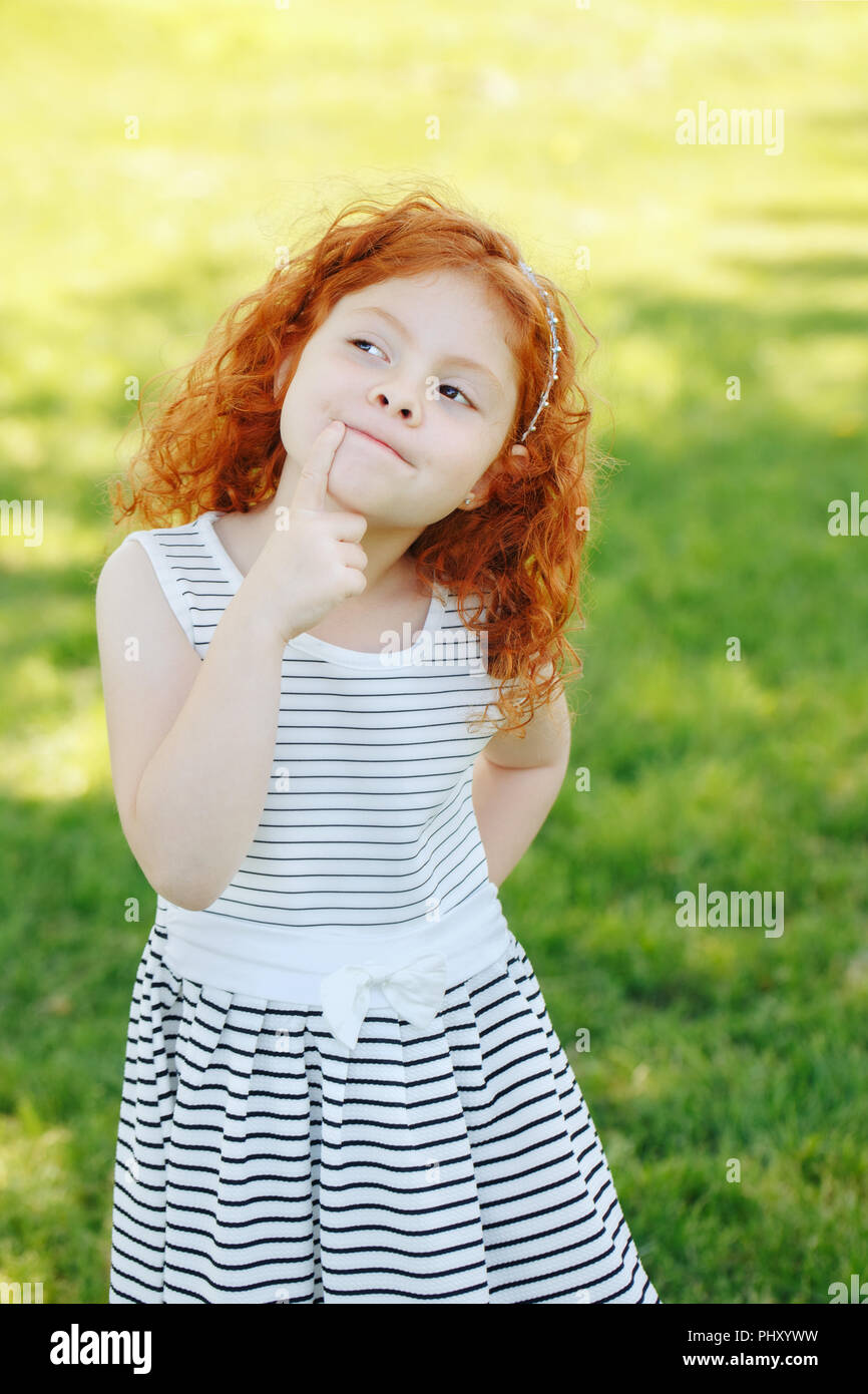 Portrait of cute adorable puzzled little red-haired Caucasian girl child in white striped dress standing in field meadow park outside thinking, having - Stock Image