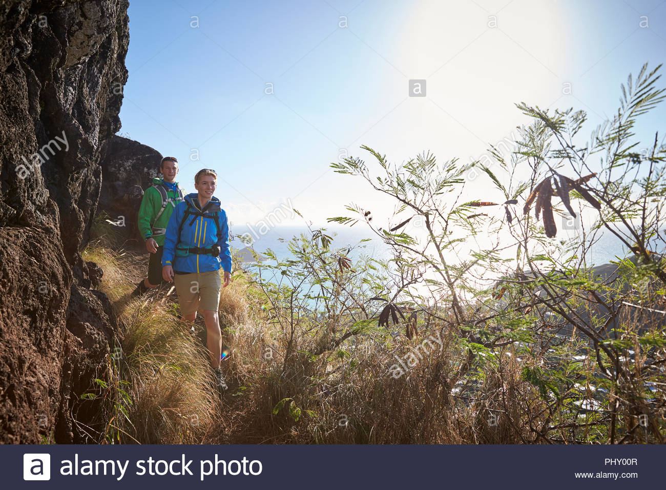 Couple hiking by cliff - Stock Image