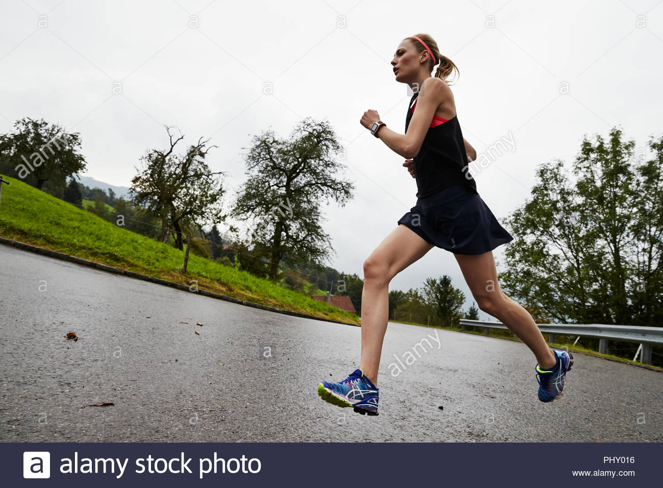 Young man running on athletics track - Stock Image