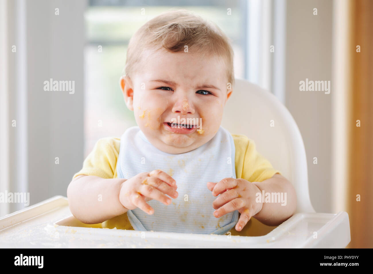 7009a61c78ec Portrait of cute crying Caucasian child boy with dirty messy face sitting  in high chair after