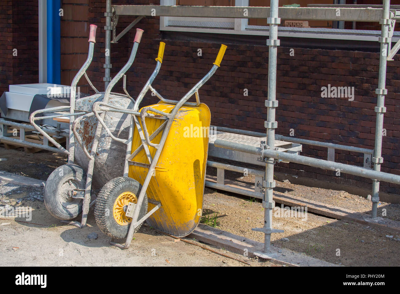 Wheelbarrows and scaffolding on construction site - Stock Image